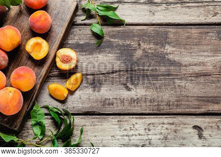 Peaches With Leaves On Dark Wooden Board With Peach In Halves. Composition With Ripe Juicy Peaches H