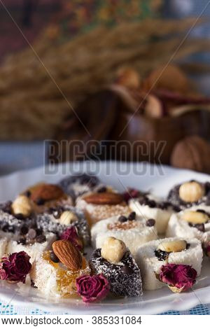 Assorted Turkish Delight On A White Plate. Traditional Yellow, White And Black Sweets With Nuts. Goo