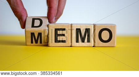 Hand Turns A Cube And Changes The Word 'demo' To 'memo' On Wooden Cubes. Beautiful Yellow Table, Whi