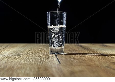 Pure Water Is Poured Into A Beautifal Glass With Bubbles On A Wooden Table With A Black Background.