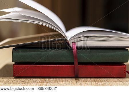 A Stack Of Books On A Wooden Table. Open Book With A Bookmark On Top Of The Stack. Close-up. Reading