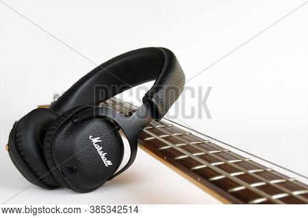 Kharkov, Ukraine - April 6, 2020 : Marshall Bluetooth Headphones, Wireless, And Fretboard From Bass