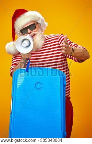 Jolly Santa Claus Santa with a megaphone and a suitcase. Christmas Holidays, winter tourism. Bright shining yellow background. Copy space.