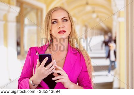 Woman In Pink Blazer Is Using Smartphone In The Shopping Center. Middle Aged Female With Phone In Ha