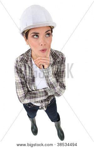 Woman in a hardhat deliberating a problem