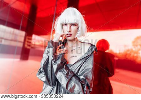 Stylish Futuristic Blonde In Cyberpunk Style On A Red Mirror Background.