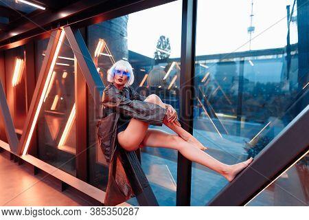 Futuristic Woman Sitting In A Neon Corridor.