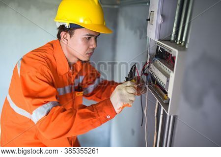 Side View Of A Handsome Asian Electrician Repairing An Electrical Box With Pliers In The Corridor.