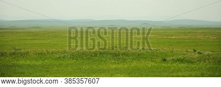 A Panoramic Shot Of The Endless Steppe Under The Summer Sunny Sky With High Mountains In The Backgro