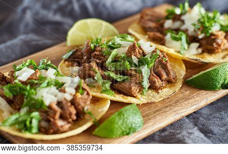 three carne asada mexican street tacos in corn tortilla with lime