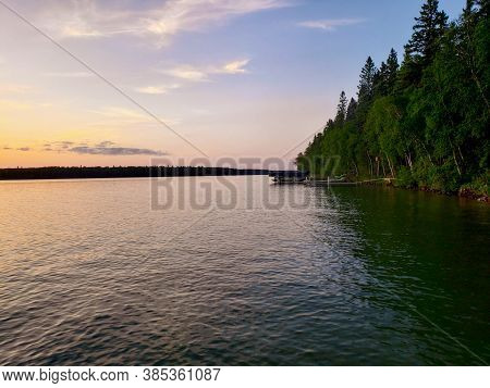 Sunset And Tree-lined Shoreline On Child's Lake In Duck Mountain Provincial Park, Manitoba, Canada