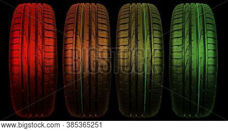 Car Tire Isolated On Black Background In Red And Green Tones. Tire Stack. Car Tyre Protector Close U