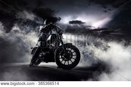 Detail of high power motorcycle chopper with man rider at night. Fog with backlights and dramatic sky on background.