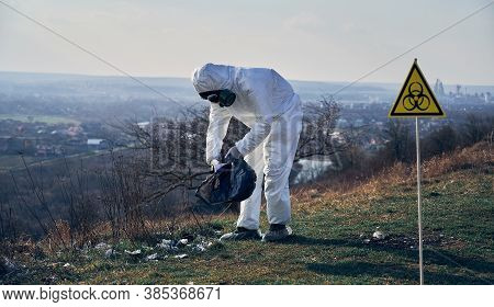 Full Length Of Ecologist In Protective Suit And Gas Mask Picking Up Garbage In Abandoned Grassy Fiel