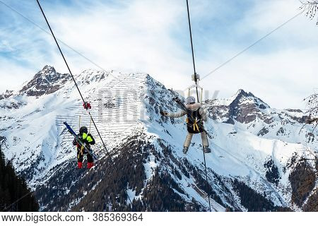 Scenic View Couple Of Tourist With Skiing Equipment Enjoy Having Fun Riding Extreme Suspended Ziplin