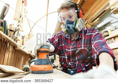 Young Adult Caucasian Mid Aged Professional Female Carpenter Grinding Raw Wood With Orbital Sander T