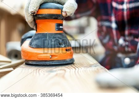 Closeup Professional Carpenter Hand Grinding Raw Wood Plank With Orbital Sander Electric Machine In