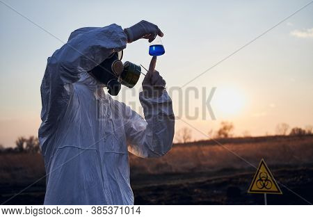 Male Ecologist In Protective Suit, Gas Mask And Gloves Holding Test Tube With Blue Liquid While Stud