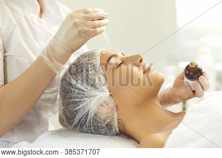 Professional Cosmetician Using Pipette To Apply Moisturizing Serum On Clients Face