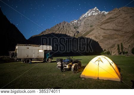 A Motorhome, A Sidecar Motorcycle And A Tent, Camping At Night In The Mountains.