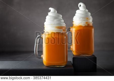 Pumpkin  cocktail with whipped cream in glass mugs. Pumpkin autumn drink for Halloween or Thanksgiving.