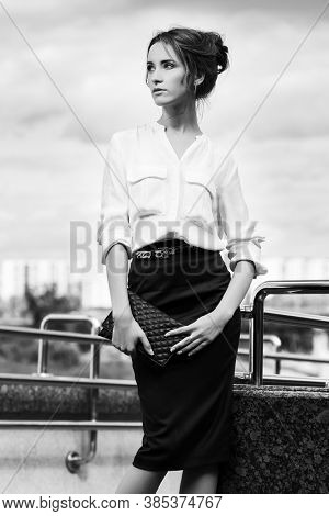 Happy young business woman with clutch bag on city street Stylish fashion model in white shirt and black pencil skirt