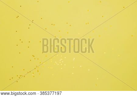 Yellow Stars On A Yelow Background. Festive Background Of Gold Confetti Stars.