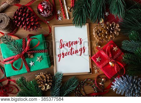 Season's Greetings Text On Cards With Gift Box Present And Ornament Element On Wood Table Background