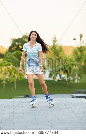 Smiling Young Woman Is Rollerskating In Summer Park.