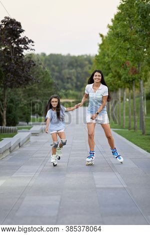 Attractive Mother And Her Cute Little Daughter Rollerskating In Summer Park. Happy Family