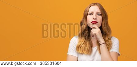 Photo Of Pensive Young Woman With Wavy Redhead Standing With Hand Raised On Chin And Looking Thought