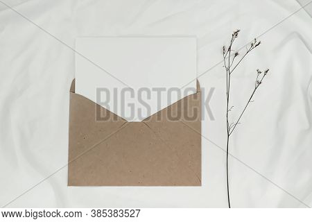 Blank White Paper Is Placed On The Open Brown Paper Envelope With Limonium Dry Flower On White Cloth