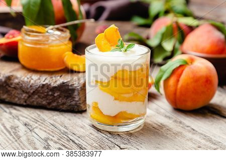 Peach Fruit Dessert In Glass Cup On Rustic Wooden Table With Fresh Peach Fruit, Peach Jam. Homemade