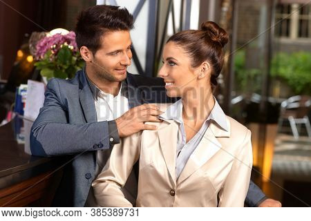 Young loving couple standing at reception desk, looking each other affectionate, smiling.