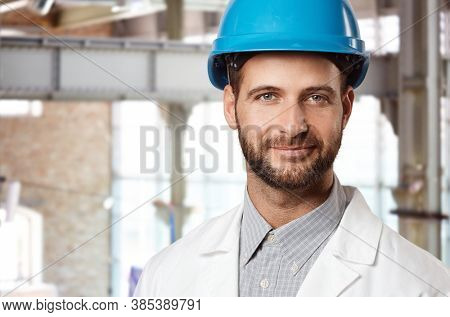 Portrait of happy engineer in hardhat inside factory building, smiling at camera.