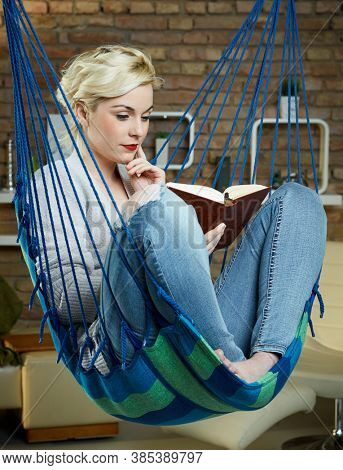 Woman sitting and reading a book in a hammock like chair at home.
