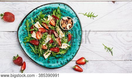 Salad With Arugula, Strawberries And Cheese Brie, Camembert. Healthy Food Diet Food Concept. Recipe