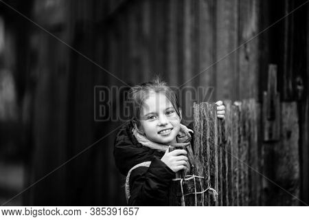 Portrait of a little girl behind a wooden fence in a village. Black and white photography.