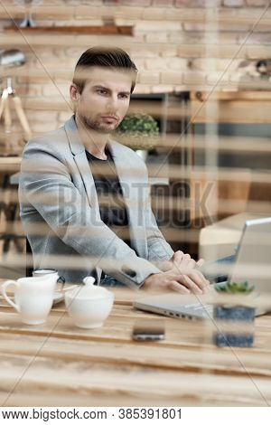 Thoughtful busy businessman working at desk, behind shutter, using laptop computer.