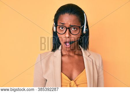 Young african american woman wearing call center agent headset in shock face, looking skeptical and sarcastic, surprised with open mouth