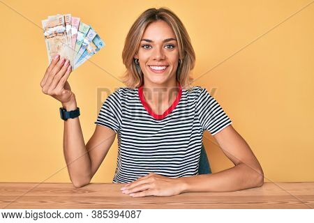 Beautiful caucasian woman holding canadian dollars looking positive and happy standing and smiling with a confident smile showing teeth