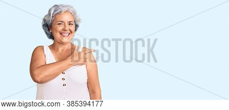 Senior woman with gray hair wearing casual clothes cheerful with a smile of face pointing with hand and finger up to the side with happy and natural expression on face