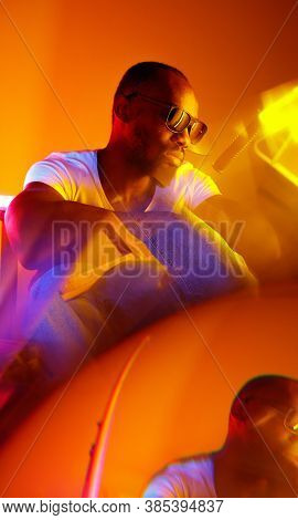 Savage. Cinematic Portrait Of Stylish Young Man In Neon Lighted Room. Bright Neoned Colors. African-