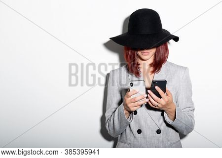 Young stylish woman wearing grey jaket and black hat using two smartphones indoor