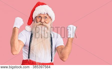 Old senior man with grey hair and long beard wearing santa claus costume with suspenders screaming proud, celebrating victory and success very excited with raised arms
