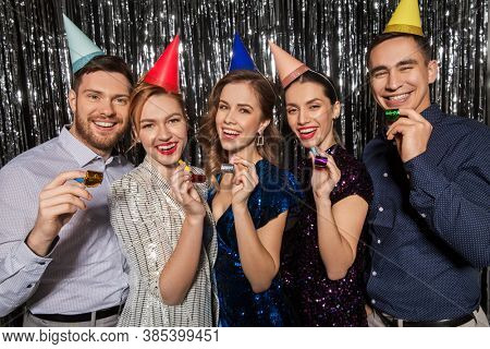celebration, fun and holidays concept - happy couple with party blowers and birthday caps