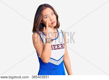 Young beautiful chinese girl wearing cheerleader uniform pointing to the eye watching you gesture, suspicious expression