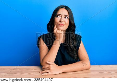 Beautiful brunette young woman wearing casual clothes sitting on the table thinking concentrated about doubt with finger on chin and looking up wondering