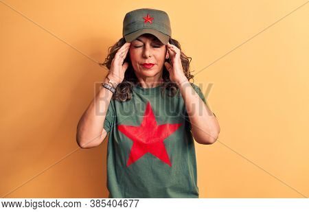 Middle age brunette woman wearing t-shirt and cap with red star symbol of communism with hand on head, headache because stress. Suffering migraine.
