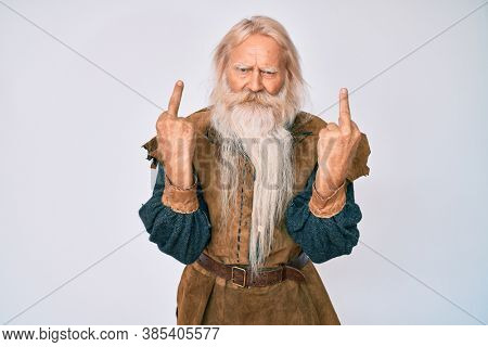 Old senior man with grey hair and long beard wearing viking traditional costume showing middle finger doing fuck you bad expression, provocation and rude attitude. screaming excited